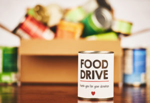 Canned goods in a box for a food drive. Can in front advertises food drive.