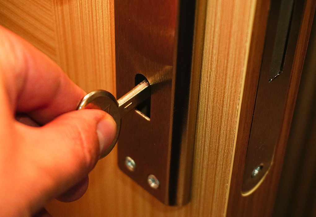 Someone unlocks a wooden door with a key in an escape room.